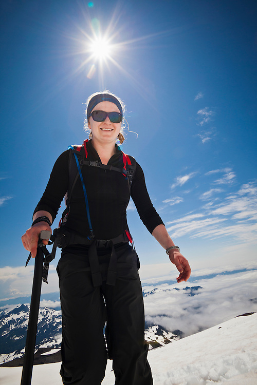 A low angle view looking up at a yound woman climber on Mount Rainier with the sun above her in the sky. Washington, USA.