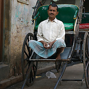 """Mohammad Asgar does not know his exact age but he knows that for the last twenty six years he has been pulling a rickshaw on the streets of Calcutta..He earns an average of about Rs100 a day (2-3 US$) out of which he pays 20 rupees as rent for his vehicle, 30 rupees for food and the rest goes to his wife and three children in Muzaffarpur, Bihar. .The hand-pulled rickshaw of Calcutta, immortalised by Dominic Lapierre's famous novel, City of Joy, will soon be a part of the history books as a bill passed by the West Bengal state assembly described the centuries-old mode of transport as """"inhumane."""".The future of about 18,000 rickshaw pullers in the city, earning an avarage daily wages of about 100 rupees ($2.5).is unclear as they call for a compensation package to help them rehabilitate into alternative jobs."""