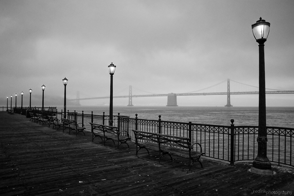Pier 7 in San Francisco looking out towards Treasure Island and the Bay Bridge. (black and white). Foggy evening with street lamps lit.