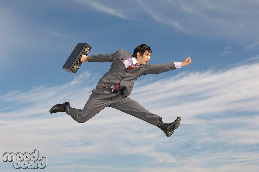 Business man running with briefcase mid-air outdoors
