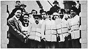 The loss of SS Titanic, 14 April 1912: Members of the ship's crew in their life jackets.  Operated by the White Star Line, SS Titanic struck an iceberg in thick fog off Newfoundland. She was the largest and most luxurious ocean liner of her time, and thought to be unsinkable.  In the collision five of her watertight compartments were compromised and she sank. Out of the 2228 people on board, only 705 survived.  A major cause of the loss of life was the insufficient number of lifeboats she carried.
