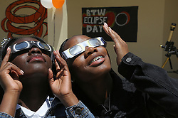 On the first day of school, 11th grade students and sisters Danyel Rolle, 15, and Stephanie Byrd, 16, right, gaze toward the sky on Monday, Aug. 21, 2017 to witness the partial eclipse at Booker T. Washington Senior High School in Miami, Fla. Photo by Carl Juste/Miami Herald/TNS/ABACAPRESS.COM