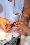 Manicurist clipping fingernails during her care for a woman client