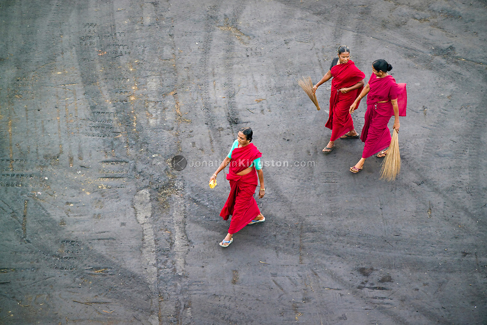 Three sari clad women prepare to sweep the docks in Chennai Port, Chennai, India.  Chennai, formerly known as Madras, is the capital of the Indian state of Tamil Nadu and is located on the Bay of Bengal.