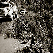 Camiones de transporte en laparte baja de la carretera de los Yungas, por donde serpentea a traves de acantilados y saltos de agua BOLIVIA. Foto: JORDI CAMI