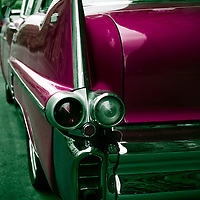 A magenta coloured 50's Cadillac viewed from the rear with chrome bumpers