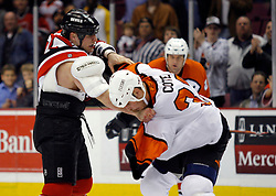 Mar 30, 2007; East Rutherford, NJ, USA; New Jersey Devils right wing Cam Janssen (25) and Philadelphia Flyers left wing Riley Cote (33) fight during the first period at Continental Airlines Arena in East Rutherford, NJ.