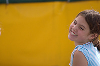 A Girl, 10-12, smiles at the camera on a sunny day, while sitting in front of a yellow trampoline mattress at the Adventure Zone, Blackcomb Mountain, Whistler, BC Canada.