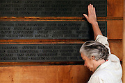 A woman touches a name on the memorial to British victims of the 9/11 attacks on the World Trade Centre. Family and friends of those killed in the attacks in New York visit the memorial to the British victims in Grosvenor Square, London,  on 11 September 2010.© under license to London News Pictures.