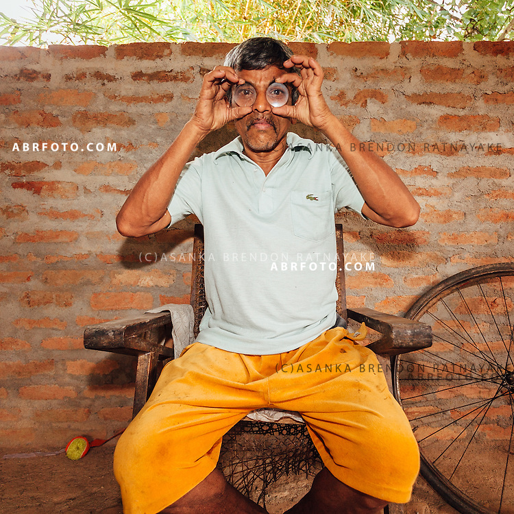 Mr Gunasoma, poses for a portrait holding up two different lenses he created by hand using rock crystal or Quartz. Photo Asanka Brendon Ratnayake