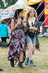 © Licensed to London News Pictures. 12/06/2015. Isle of Wight, UK.  Pretty female festival goers in nice dresses and clothes shelter from the light rain with with a pretty umbrella at Isle of Wight Festival 2015 on the morning of Friday Day 2.  Yesterday the weather was hot and Sunny.  Today rain is forecast.  This years festival include headline artists the Prodigy, Blur and Fleetwood Mac.  Photo credit : Richard Isaac/LNP