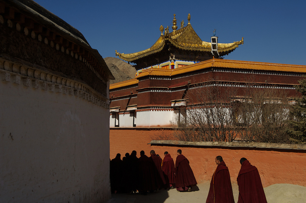 Buddhist monks wearing heavy maroon robes head towards the main prayer hall of Labrang Monastery, for Losar prayers, at Tibet's new year.<br />