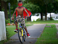 "7/24/13 - Oziah Wright, 6, rides his bicycle down Climax Street in Graham, N.C. on the afternoon of Wednesday, July 24, 2013. When asked if he had a superhero name, he said that he refers to himself as ""Cyclon."" (AP Photo/Burlington Times-News, Scott Muthersbaugh)"