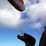 A para glider takes off above the hillside of Pedro Bonita high in the hills of Rio de Janeiro. Pilots of hang gliders and para gliders take tourists for tandem flights with breathtaking views of the city before landing on Sao Conrado beach. Rio de Janeiro,  Brazil. 9th September 2010. Photo Tim Clayton