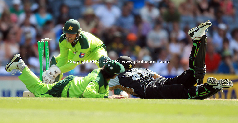 Pakistan wicketkeeper Umar Akmal takes the bails off to run out Martin Guptill. Twenty20 International Cricket match between The New Zealand Black Caps and Pakistan at Eden Park on Boxing Day, Sunday 26 December 2010. Photo: Andrew Cornaga/photosport.co.nz