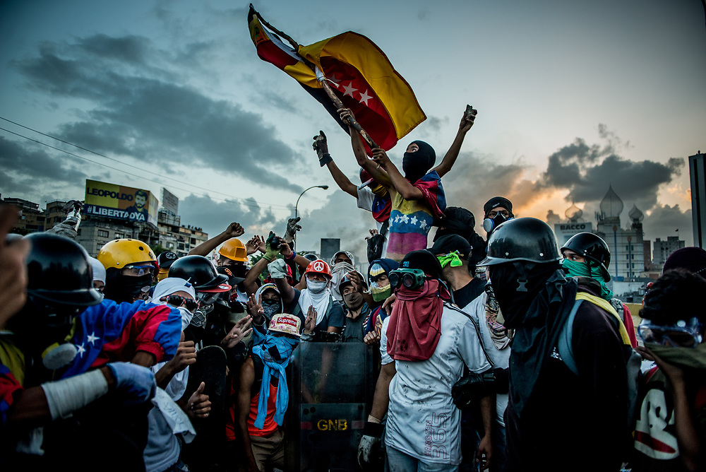 CARACAS, VENEZUELA - MAY 26, 2017:  Anti-government protesters celebrate after taking back control of the main highway that runs through Caracas from government security forces. The streets of Caracas and other cities across Venezuela have been filled with tens of thousands of demonstrators for nearly 100 days of massive protests, held since April 1st. Protesters are enraged at the government for becoming an increasingly repressive, authoritarian regime that has delayed elections, used armed government loyalist to threaten dissidents, called for the Constitution to be re-written to favor them, jailed and tortured protesters and members of the political opposition, and whose corruption and failed economic policy has caused the current economic crisis that has led to widespread food and medicine shortages across the country.  Independent local media report nearly 100 people have been killed during protests and protest-related riots and looting.  The government currently only officially reports 75 deaths.  Over 2,000 people have been injured, and over 3,000 protesters have been detained by authorities.  PHOTO: Meridith Kohut