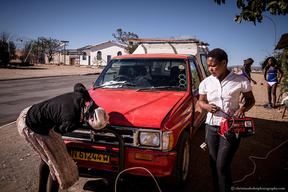 (2013) Some of the women are fixing the battery of Father Hermanns car in front of the shelter in Katutura.