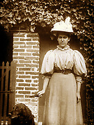 French woman stands next to a doorway with a dog. Circa 1900