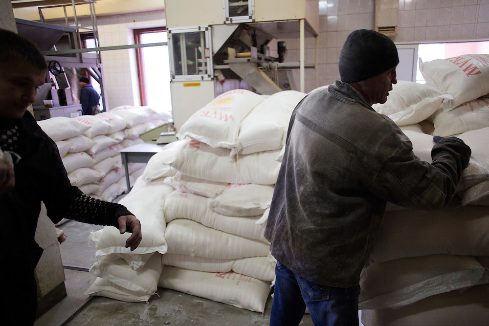 Mine workers stack sacks of sugar and flour from a humanitarian aid convoy from Russia at Zasyadtko Mine on March 7, 2015 in Donetsk, Ukraine.