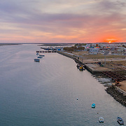 Sunrise aerial panoramic seascape view of Olhao dockyard, waterfront to Ria Formosa natural park with Armona island in background. Algarve. Portugal.