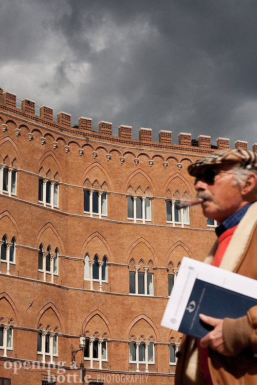 A man smoking a cigar strolling through Piazza del Campo, Siena, Tuscany, Italy.