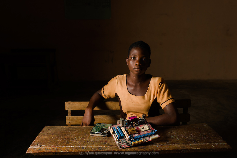 Peace (17), pictured on 15 May 2014, is a student in the Volta Region of Ghana. Like all Ghanaian students, ICT is one of her core subjects, but her school has neither electricity nor computers, so she and her fellow students must rely entirely on theoretical knowledge to pass their examinations. Together with a hand-drawn poster of a keyboard, the old motherboard, hard drive and CD drive in front of her are the school's only ICT resources.