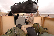 SSG Christopher Olson (right) helps soldiers with their bags, while transiting through Manas Air Base, Kyrgyz Republic on 15 March 2006. He has completed a 12-month tour in Afghanistan and heads home.  He is stationed with the Headquarters and Service Company (HSC) 864 Engineering Combat Battalion, Ft. Louis. Wash. The Manas population is normally more than 1,000, but surges to 2,500 during Army rotation periods. (U.S. Air Force photo by Master Sgt. Lance Cheung)<br />