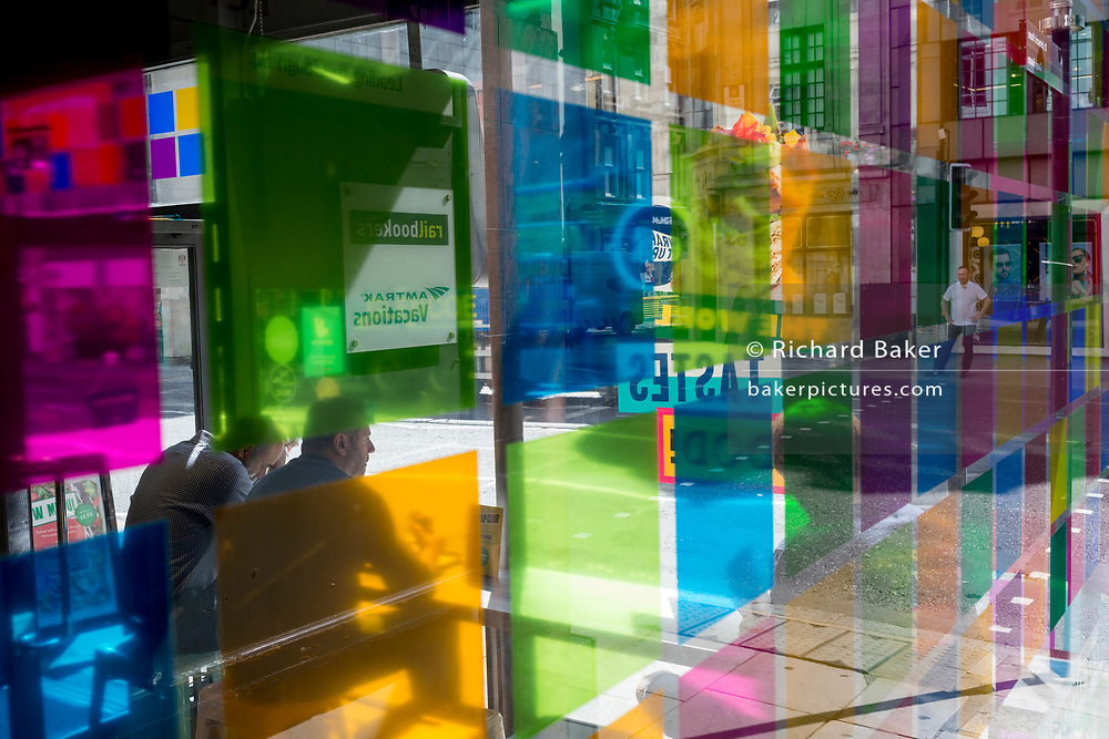 Figures seen through coloured-squared light in a corner cafe on Fleet Street in the City of London, the capital's financial district (aka the Square Mile), on 22nd August 2019, in London, England.