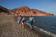 Marine biologist Bruce Mate walks and talks with young girl and her mother on Sea of Cortez beach at Puerto Gato; Baja, Mexico.