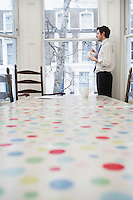 Man standing at window in dining room
