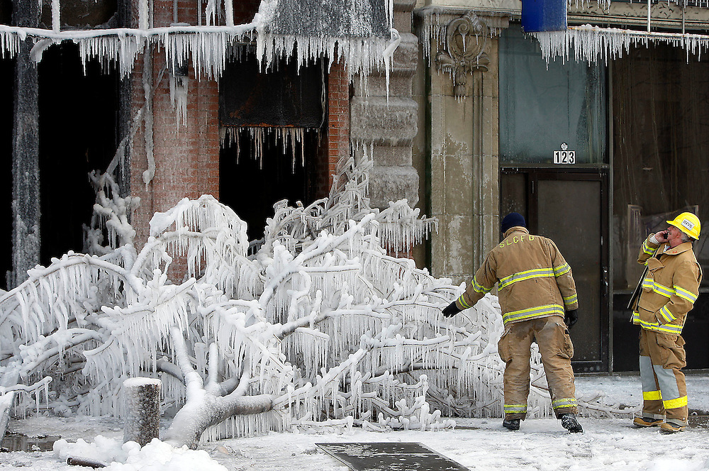 Two Salt Lake City firemen check out the Ice which hangs from the front of the old DV8 nightclub and from a tree that was cut down in front of the building after fire crews put out a blaze which gutted the building the previous night. Photo takent in Salt Lake City, Utah Thursday, Jan.24, 2008. August Miller/ Deseret Morning News .