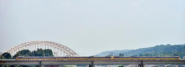 Nederland, Nijmegen, 10-7-2014De aanloop naar de spoorbrug over de rivier de Waal. Er rijdt een trein overheen. Op de achtergrond de oude Waalbrug, een verkeersbrug.Foto: Flip Franssen/Hollandse Hoogte