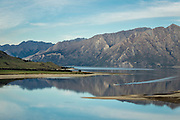 Boating on the glassy surface of Lake Hawea, Central Otago, New Zealand.