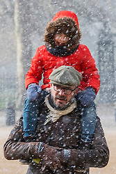 © Licensed to London News Pictures. 26/02/2018. London, UK. A little boy is carried on his father's shoulder as snow falls on Horse Guards Parade in Central London. Severe cold, blizzards and heavy snow are expected as the 'Beast from the East' brings freezing Siberian air to the UK. Photo credit: Rob Pinney/LNP