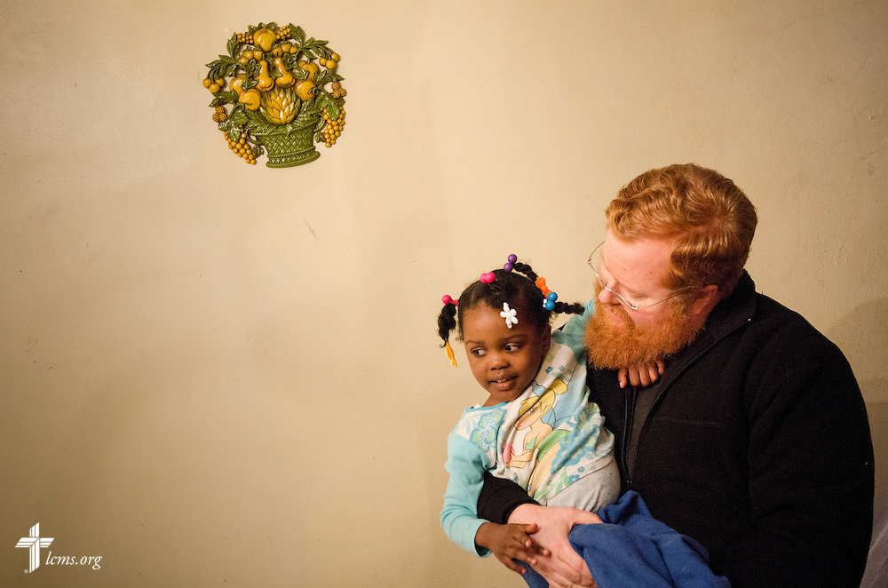 The Rev. Roy Axel Coats, pastor of Lutheran Church of the Redeemer, holds a child of Liberian catechist Augustine Tarley as he makes a home visit near the church on Thursday, March 27, 2014, in Baltimore, Md. LCMS Communications/Erik M. Lunsford
