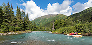 Whitewater rafters rafting down Sixmile Creek on the Kenai Peninsula in Southcentral Alaska. Summer. Afternoon.