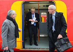 © Licensed to London News Pictures. 14/05/2013. London, UK (Left to right) Transport for London's Commissioner, Sir Peter Hendy CBE, Boris Johnson, David Higgins, Network Rail Chief Executive on a train back to Waterloo Station in Central London. The Mayor of London, Boris Johnson, leads a short walkabout around Wimbledon High Street to meet local people as he helps launch a public consultation on proposed routes for Crossrail 2. Today 14th May 2013. Photo credit : Stephen Simpson/LNP