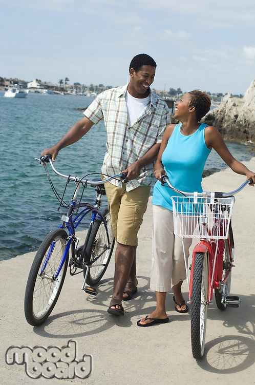 Middle-aged couples standing at promenade with bicycles