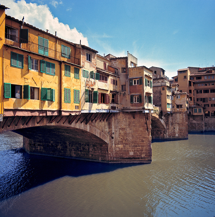 The Arno River flows beneath the Ponte Vecchio in Florence, Italy.