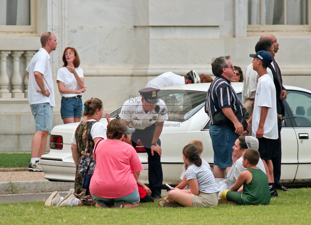 Police officers take statements from witnesses after a shooting erupted on Capitol Hill July 24, 1998 in Washington, DC. Two US Capitol police officers were killed in the incident, one person wounded and the lone gunmen was wounded and taken into custody.