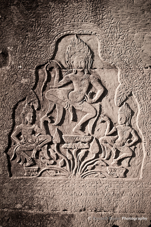 A bas relief of celestial goddesses dancing on lotus flowers at The Bayon temple in the walled city of Angkor Thom, Siem Reap, Cambodia