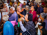 04 SEPTEMBER 2017 - BANGKOK, THAILAND: Elderly people from riverfront communities in Bangkok wait for a food distribution to start at Chaomae Thapthim Shrine. About 1,000 people came to the shrine for the annual food distribution. Staples, like rice and cooking oil, are donated to the shrine throughout the year and donated to poor people from the communities around the shrine. Food distributions like this are a tradition at Chinese shrines in Bangkok and a common way of making merit for the people who donate the staples.     PHOTO BY JACK KURTZ