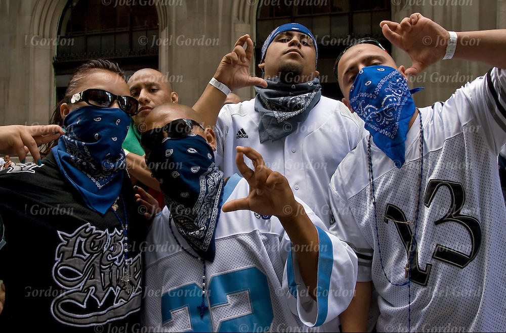 California's South-Side 13 gang members wearing blue bandana masks  and sunglasses, posing for the camera making gang sign at the end of the Mexican Day Parade in New York City.<br />
