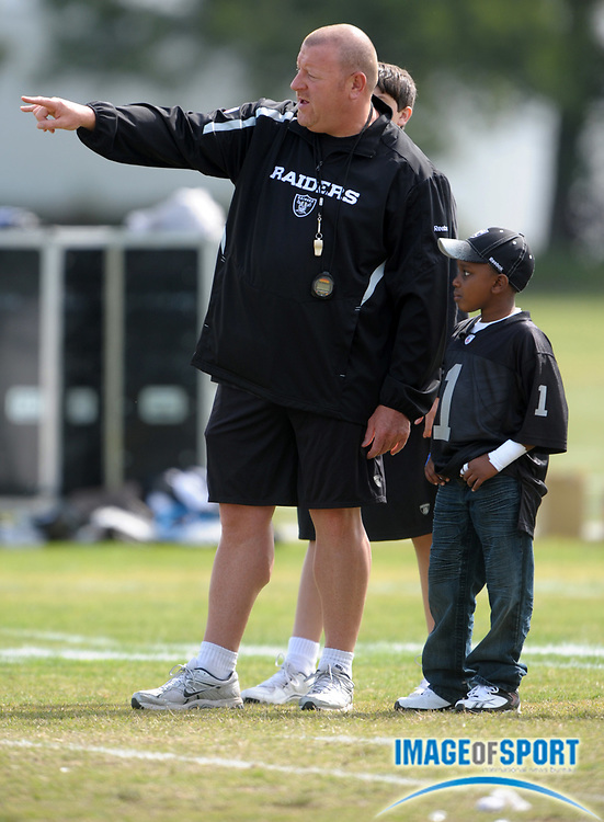 May 26, 2010; Alameda, CA, USA; Oakland Raiders coach Tom Cable (left) visits with Make-A-Wish Foundation child Jailen Cooper at organized team activities at the Oakland Raiders practice facility.