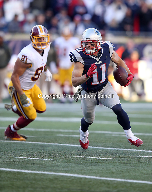 New England Patriots wide receiver Julian Edelman (11) runs away from Washington Redskins outside linebacker Ryan Kerrigan (91) as he runs for a first down called back due to a fourth quarter penalty during the 2015 week 9 regular season NFL football game against the Washington Redskins on Sunday, Nov. 8, 2015 in Foxborough, Mass. The Patriots won the game 27-10. (©Paul Anthony Spinelli)