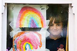 © Licensed to London News Pictures. 23/04/2020. London, UK. A girl looks out of the window next to hand painted pictures of colourful rainbows displayed in a house in north London. Rainbows are used as a symbol of peace and hope. Photo credit: Dinendra Haria/LNP