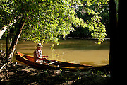 A fly fisherman prepares his rod to fish for smallmouth bass in the Olentangy river in Central Ohio, while seated in a handmade wooden canoe.