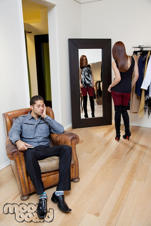 Tired young man sitting on armchair while woman looking at herself in mirror
