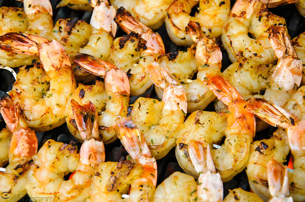 Shrimp skewers cooked over a low flame.