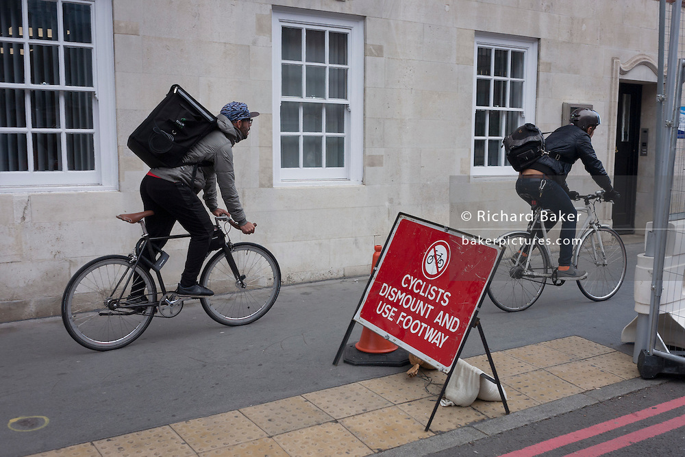 Two delivery couriers ignore a cyclist's dismount sign on the southern side of London's Tower Bridge, closed for repairs to traffic and disrupting this major Thames crossing and surrounding roads for the next three months.